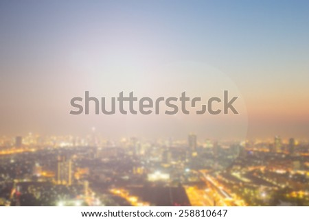 Blurred night city background with bokeh flare light.blurry view of downtown/urban backdrop:blur city plan and skyline metropolis district concept.shining evening sky golden hour time.warm tone color - stock photo