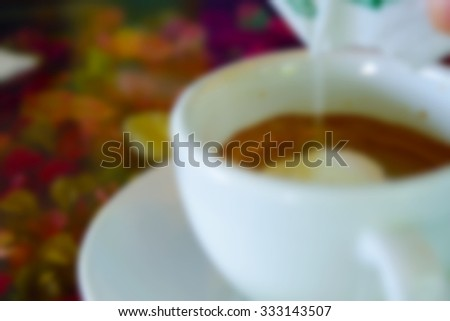 Blurred of Fill in creamer in coffee in white cup on table with flower - stock photo