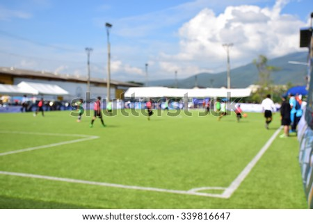Blurred of young kids playing a youth soccer match outdoors - stock photo
