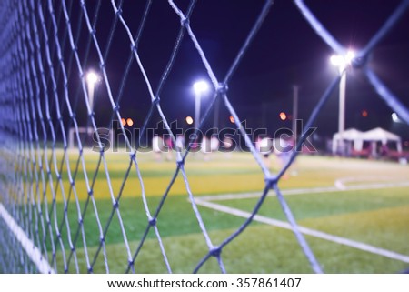 Blurred of young kids playing a youth soccer match outdoors on night time. - stock photo