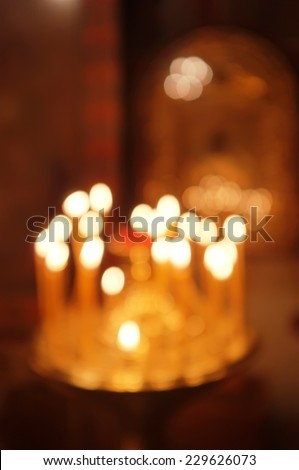 Blurred orthodox Christmas background. Abstract unfocused candle lights in front of old icon backdrop. - stock photo