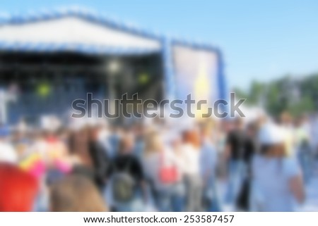 Blurred people attend open-air concert - stock photo