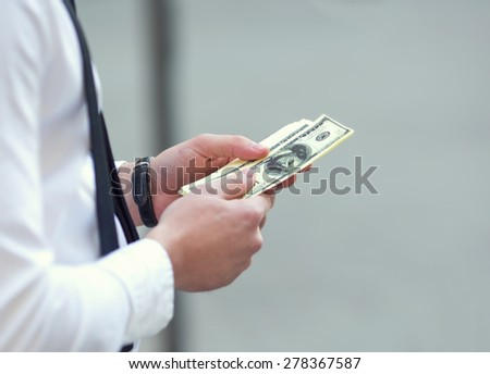Blurred people image background. Business finance market. Man holding American dollars in hands. Man recounts money, currency, dollar. One hundred dollar bills. Only hands with money close up. Bribe - stock photo