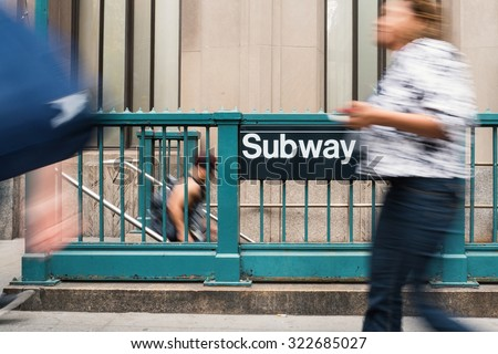 Blurred people walking in front of NYC subway entrance. The NYC Subway is one of the oldest and most extensive public transportation systems in the world, with 468 stations.  - stock photo
