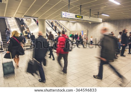 Blurred people walking inside train station or airport, with luggage and bags. There are some escalators on background, with people walking on both directions. Travel and urban lifestyle concepts.  - stock photo