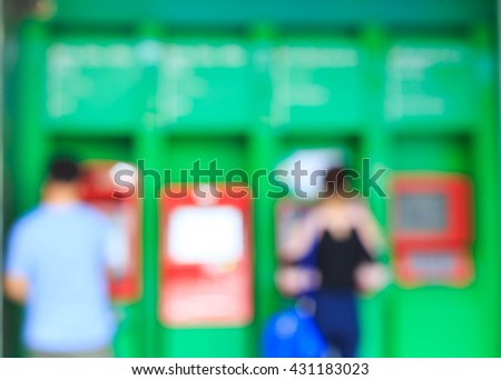 Blurred people withdraw money from atm - stock photo