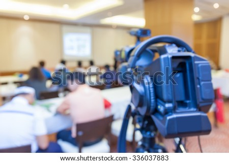 Blurred photo of conference meeting and broadcasting camera. - stock photo