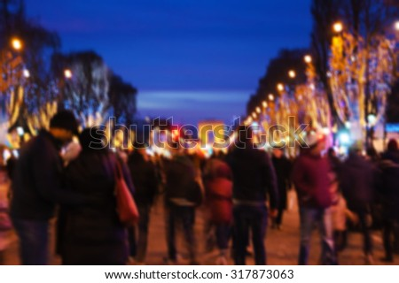 Blurred photo of people promenade at Champs Elysees with Christmas festive illumination and Arch of Triumph seen at background. Paris in winter.  - stock photo