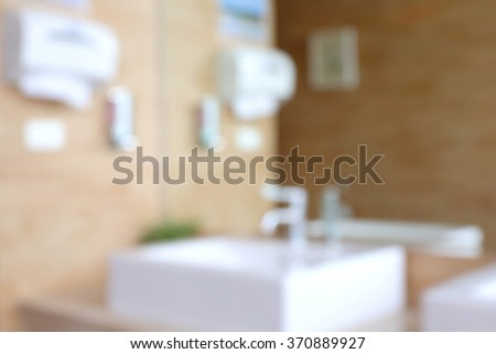 Blurred photo of public empty restroom with sink and tap. - stock photo