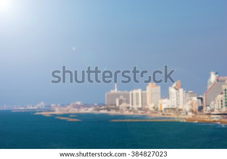 Blurred photo of Tel Aviv beach skyline. Toned photo with lens flare effect. - stock photo