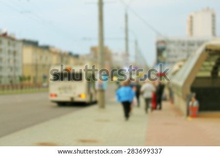 Blurred public transport stop with a bus waiting for the passengers - stock photo