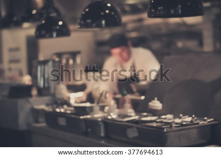 Blurred Restaurant chef: Chef cooking in the open kitchen, customer can see they cooking at food counter - stock photo