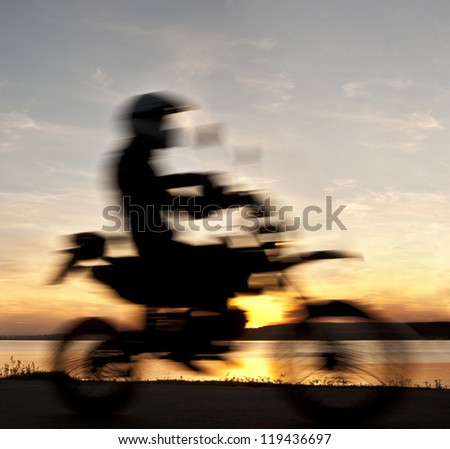 blurred silhouette of a sports motorcycle riding on the road along the coast seaming against orange sky - stock photo
