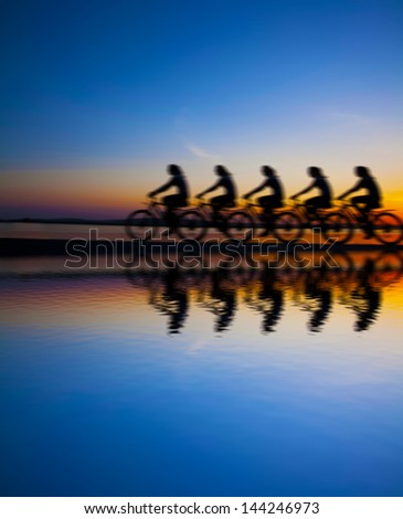 Blurred silhouette of people Image sporty company friends on bicycles outdoors against sunset Silhouette with reflection on water  A lot phases of motion of single cyclist along the shoreline coast - stock photo