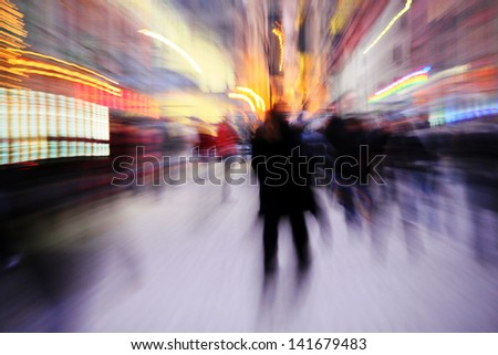 Blurred silhouettes of people in city - stock photo