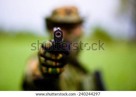 Blurred soldier hang pistol. - stock photo