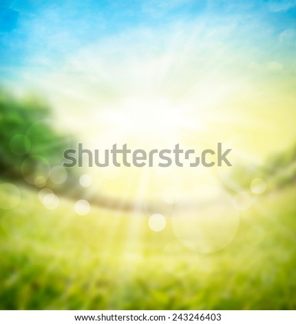 blurred spring summer nature background with green meadow, trees on  horizon and sun rays with bokeh - stock photo