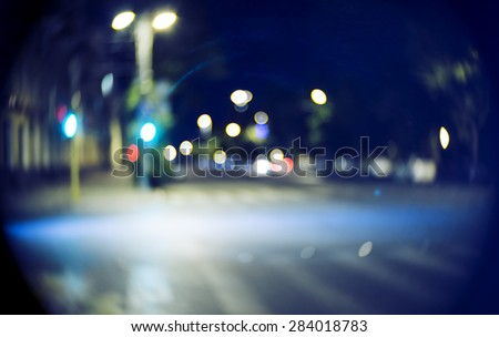 Blurred street at night time. Vintage looking shot made with very old C-mount cinema lens - stock photo