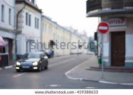 Blurred street with a car and a wrong way sign - stock photo