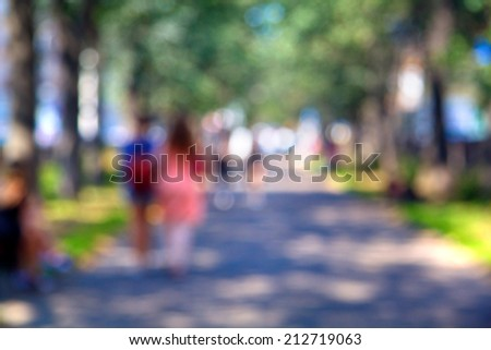 Blurred unfocused city view at day time. Unfocused people in the theme park - stock photo
