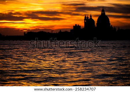 Blurred unsharp black silhouette background of the Saint Mary of Health Basilica di Santa Maria della Salute church in orange sunset on sharp waves of the Grand Canal in the foreground - stock photo