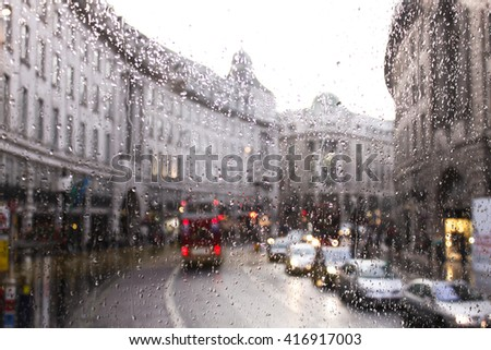 blurred view of road traffic in London on a rainy day through the bus window. raindrops on the glass window of the bus. - stock photo