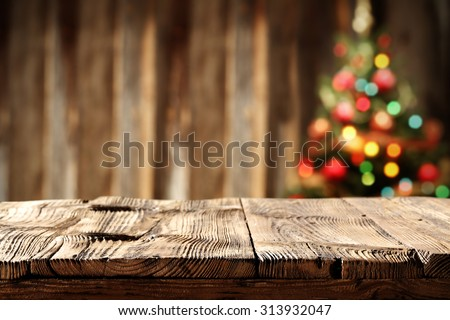 blurred wall background with xmas tree of few colors lights and shabby table  - stock photo