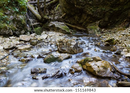 Blurred water in motion among rocks in a river. Slovak Paradise, Slovensky Raj National Park, Slovakia - stock photo