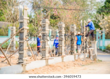 Blurred worker pouring cement to concrete pillar mold for house construction 