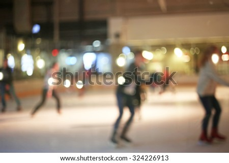 Blurred young people skating on the ice rink - stock photo