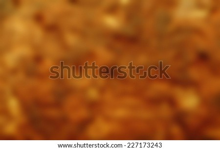 Blurry abstract gold-brownish wallpaper background with texture. - stock photo