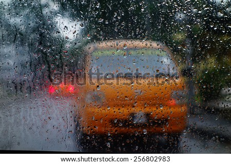 blurry abstract view of school bus driving on road from window during raining season - stock photo
