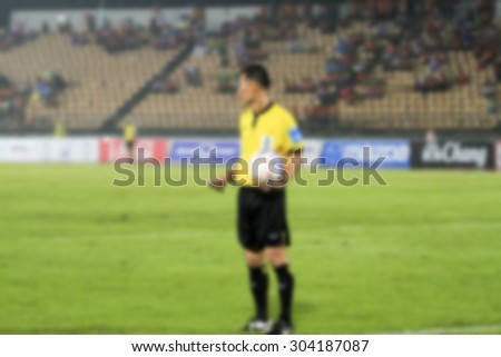 blurry Assistant football referee and Referee's flag and referee holding ball on hand - stock photo