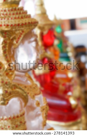 blurry defocused image of clear resin buddha statue wearing asian golden jewelry for background - stock photo