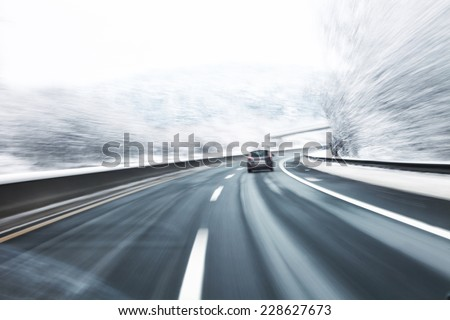 Blurry fast turn at the icy snow road with one car in the foreground. Motion blur visualizies danger of the high speed and dynamics. - stock photo