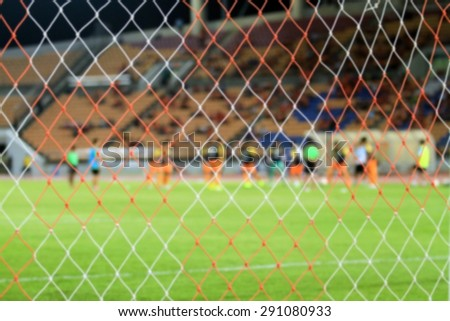 blurry football and soccer goal net pattern and football player training - stock photo