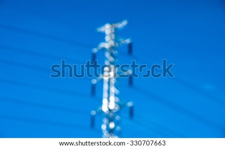 Blurry high voltage post or power transmission line tower and blue sky - stock photo