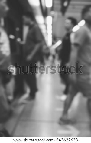 blurry image of passenger boarding train, monochrome - stock photo