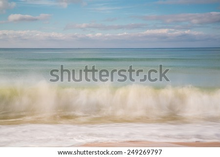 blurry motion of waves splashing on the beach - stock photo