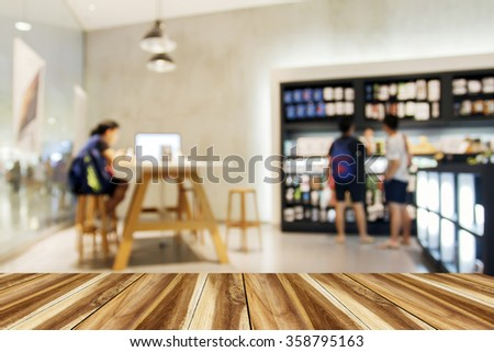 Blurry of people walking and test mobile phone shop at shopping center/supermarket/mall with Perspective wood - stock photo