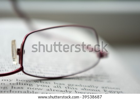 Blurry reading glasses on an open book - stock photo