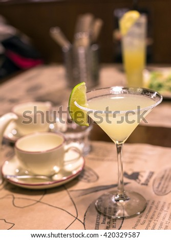 Blurry view of lime cocktail glass with salt crystals on its edge in restaurant - stock photo