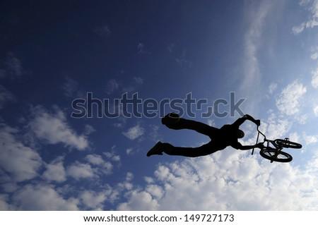Bmx bike rider is flying on his bike doing trick - stock photo