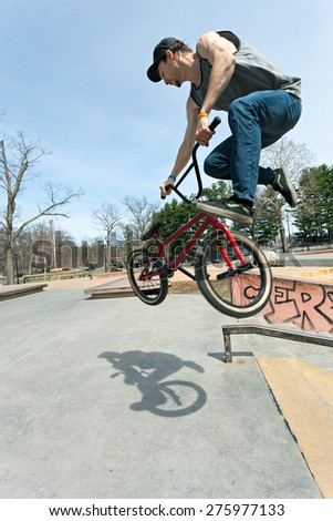BMX rider athlete spinning his entire bike mid air.  Shallow depth of field and slight motion on rider due to action. - stock photo
