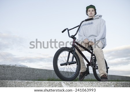 Bmx rider jumping off concrete wall performing a trick - stock photo