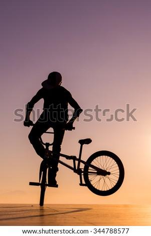 BMX silhouette rider at sunset  - stock photo