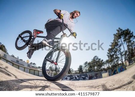 Bmx stunt performed at the top of a mini ramp on a skatepark. - stock photo