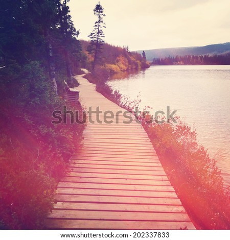 Board walk or path around lake with instagram effect - stock photo