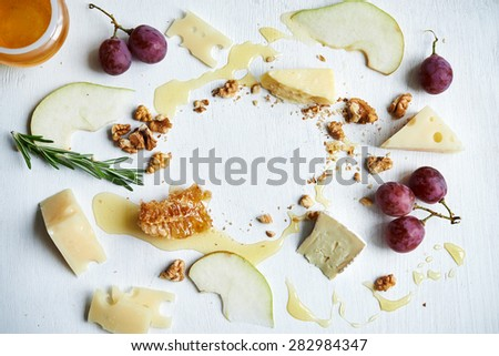 board with cheese, honey, fruits and nuts. place for copy space - stock photo