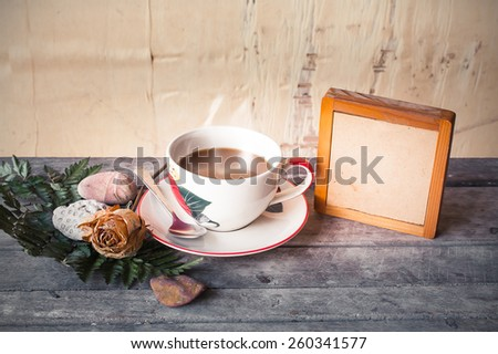 board with coffee and dry rose flower on wooden table in vintage tone - stock photo